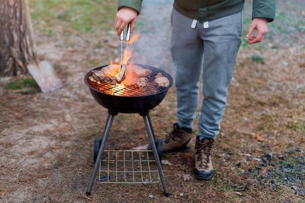 Hombre cocinando, solo manos, está asando carne o filete para un plato. deliciosas carnes a la parrilla. barbacoa fin de semana. enfoque selectivo.