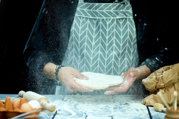 El hombre, cocinero cocina tira la masa, volando, congelando en movimiento.