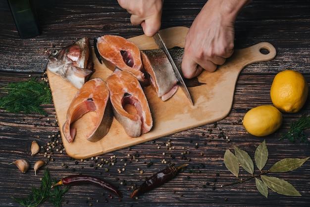 Hombre cocinero corta un cuchillo en manos de trucha. pescado rojo fresco crudo cortado