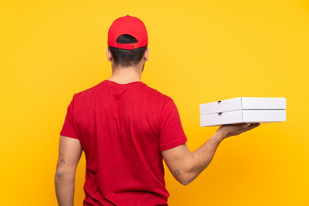 Hombre cogiendo cajas de pizza sobre pared aislada