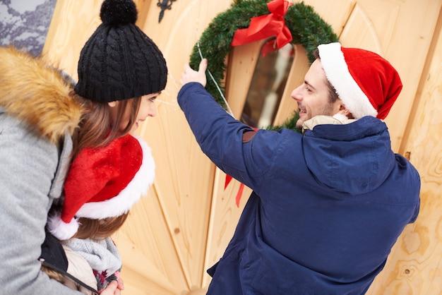 Hombre colgando la corona de navidad en la puerta