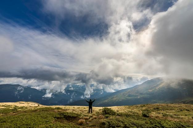Hombre en la colina cubierta de hierba con los brazos levantados en el cielo azul nublado y verdes montañas boscosas.