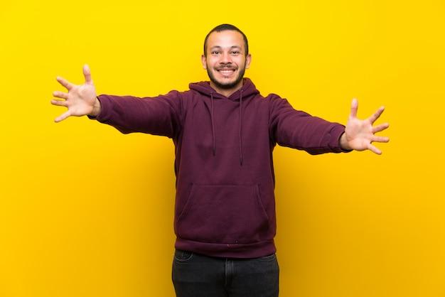 Hombre colombiano con sudadera en pared amarilla presentando e invitando a venir con la mano.