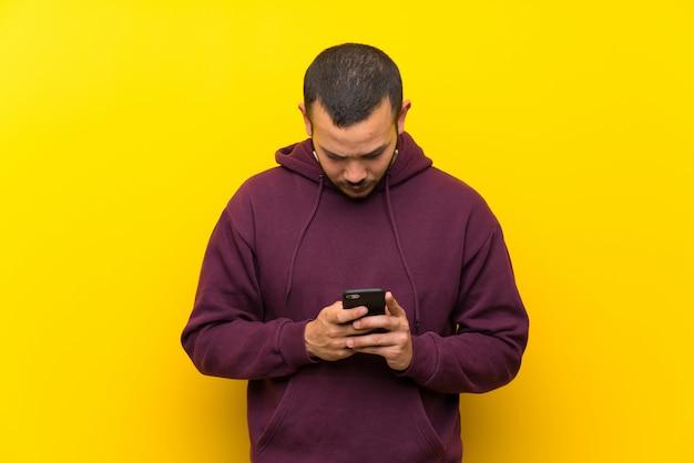 Hombre colombiano con sudadera sobre muro amarillo enviando un mensaje con el móvil.