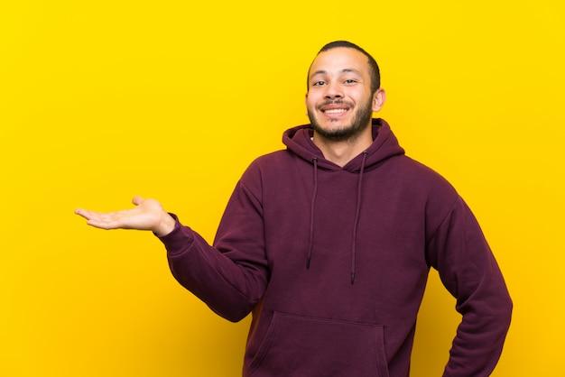 Hombre colombiano con sudadera sobre una pared amarilla con copyspace imaginario en la palma