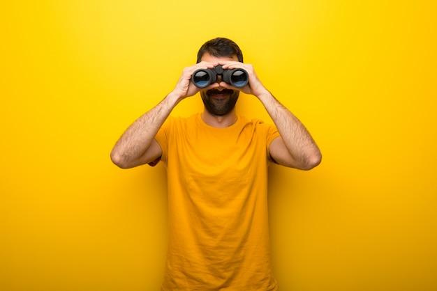 Hombre en color amarillo vibrante aislado y buscando algo en la distancia con binoculares