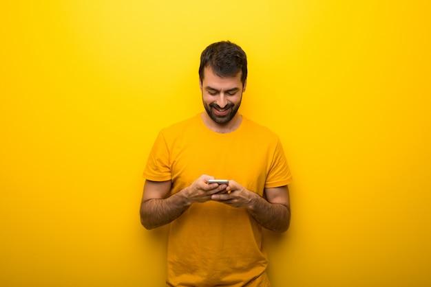 Hombre en color amarillo vibrante aislado enviando un mensaje o correo electrónico con el móvil
