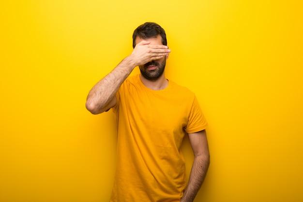 Hombre en el color amarillo vibrante aislado que cubre ojos por las manos. no quiero ver algo