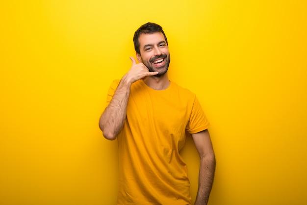 Hombre en el color amarillo vibrante aislado que hace gesto del teléfono. vuelve a llamarme señal