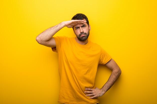 Hombre en el color amarillo vibrante aislado que mira lejos con la mano para mirar algo