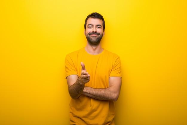 Hombre en color amarillo vibrante aislado que sacude las manos para cerrar un buen negocio