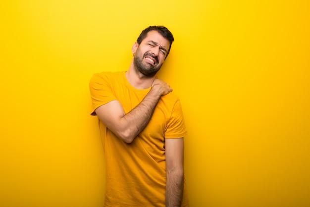 Hombre en color amarillo vibrante aislado que sufre de dolor en el hombro por haber hecho un esfuerzo