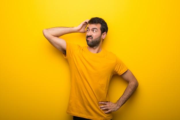 Hombre en color amarillo vibrante aislado que tiene dudas mientras se rasca la cabeza