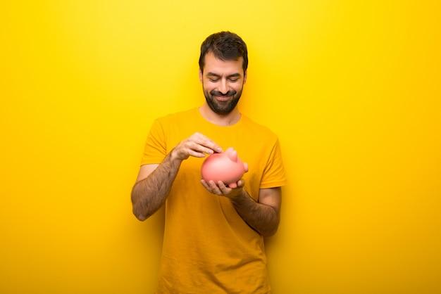Hombre en color amarillo vibrante aislado que toma una alcancía y feliz porque está lleno