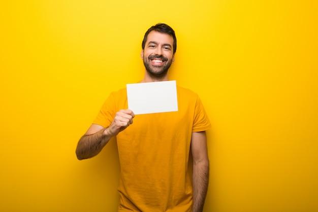 Hombre en color amarillo vibrante aislado sosteniendo un cartel blanco vacío para insertar un concepto