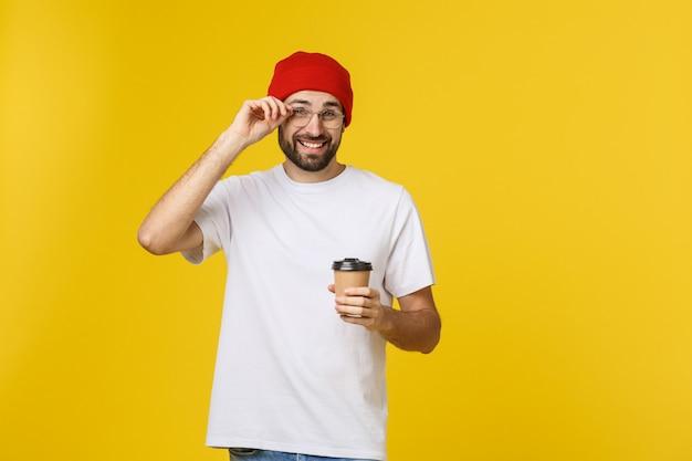 Hombre en color amarillo vibrante aislado tomando un café en una taza de papel para llevar y sonriendo porque comenzará bien el día.