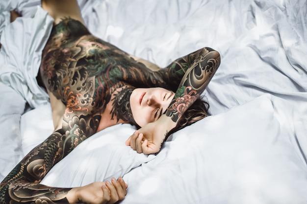 Hombre con coloridos tatuajes descansando sobre una sábana blanca