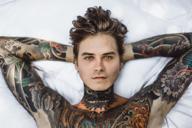 Hombre con coloridos tatuajes posando en una sábana blanca