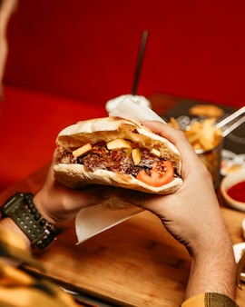 El hombre come doner en pan con carne, tomate y papas fritas
