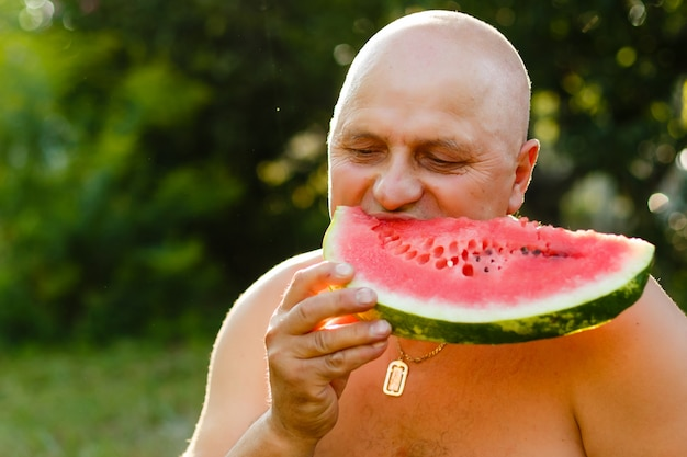 El hombre come una sandía en un jardín.
