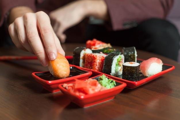 El hombre come sushi roll con las manos