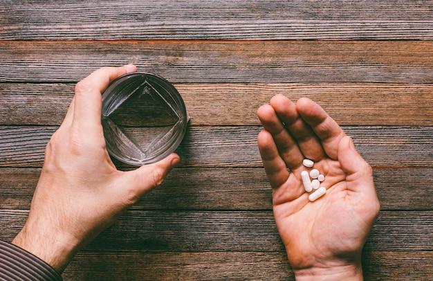El hombre va a comer pastillas y cápsulas y beber con agua.