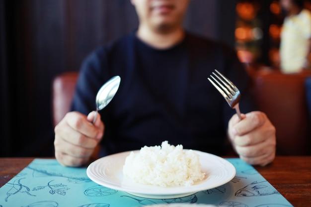 Hombre comiendo arroz disfrutando de una comida en el restaurante.
