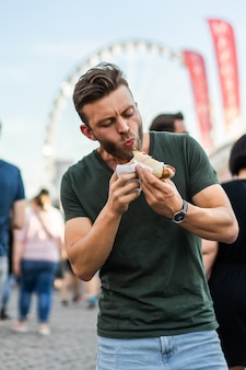 Hombre comiendo comida callejera. perritos calientes de la calle