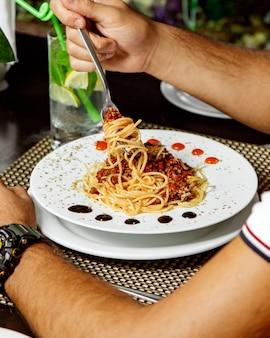 Hombre comiendo espaguetis a la boloñesa con hojas de menta seca