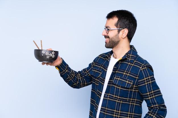 Hombre comiendo fideos sobre pared aislada