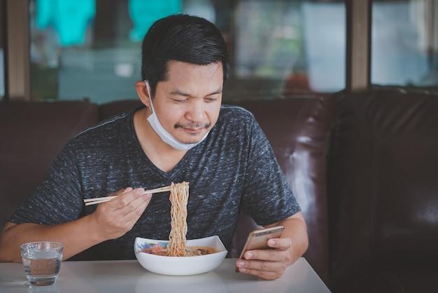 Hombre comiendo fideos y usando un teléfono inteligente en casa durante el bloqueo debido a la situación de la epidemia de covid-19
