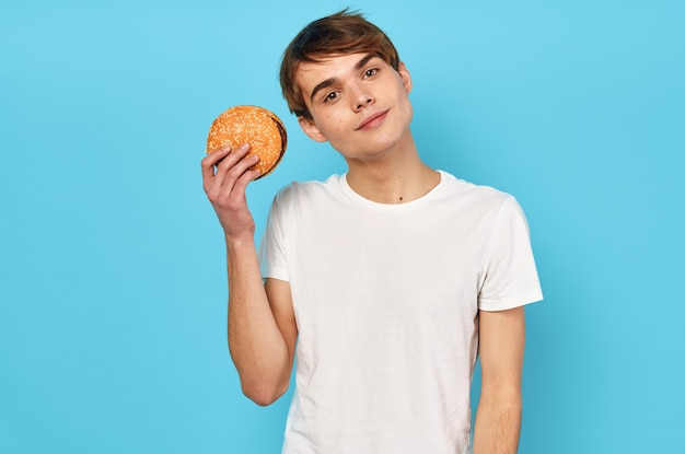 Hombre comiendo hamburguesa en camiseta blanca dieta alimentos estilo de vida fondo azul