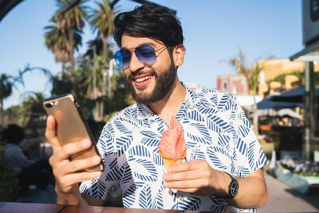 Hombre comiendo helado y usando su teléfono.