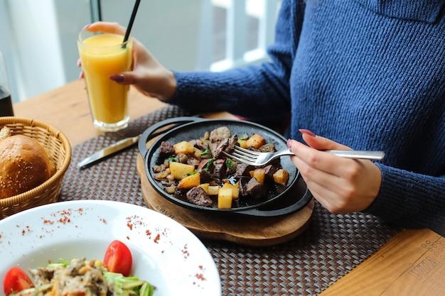 Hombre comiendo hígado frito con papa, cebolla y verduras y bebiendo jugo