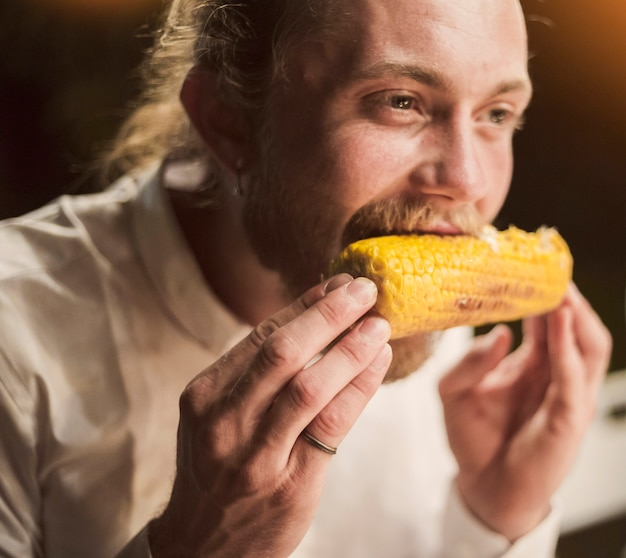 Hombre comiendo maíz con placer