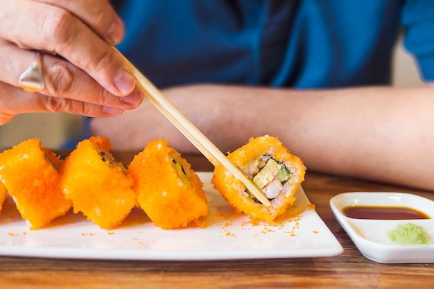 Hombre comiendo maki sushi