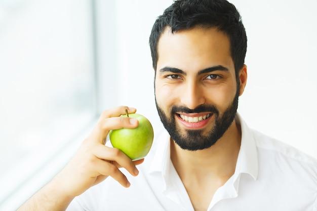 Hombre comiendo manzana. muchacha hermosa con los dientes blancos que muerden la manzana. imagen de alta resolución