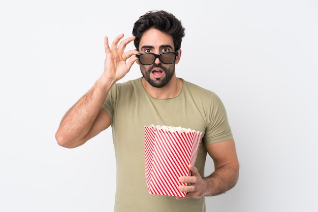 Hombre comiendo palomitas mientras mira una película sobre una pared aislada