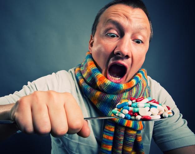 Hombre comiendo pastillas