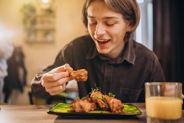 Hombre comiendo pollo frito con salsa en un café