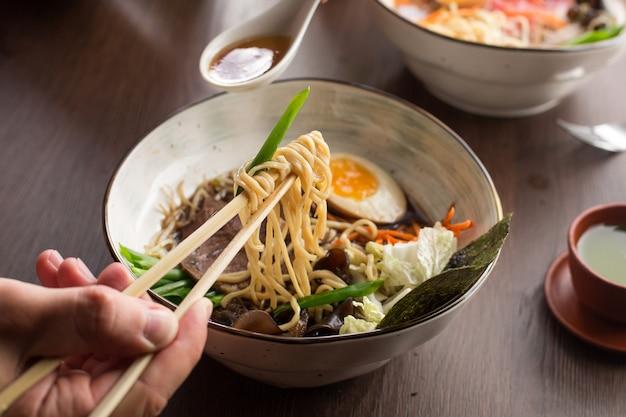 Hombre comiendo ramen asiático con atún y fideos en un restaurante