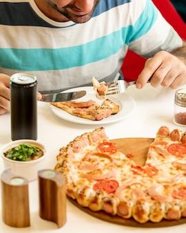 Hombre comiendo una rebanada de pizza de salchicha en el restaurante