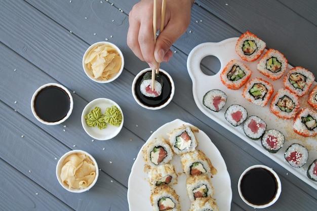 Hombre comiendo rollos de sushi en la mesa de madera gris