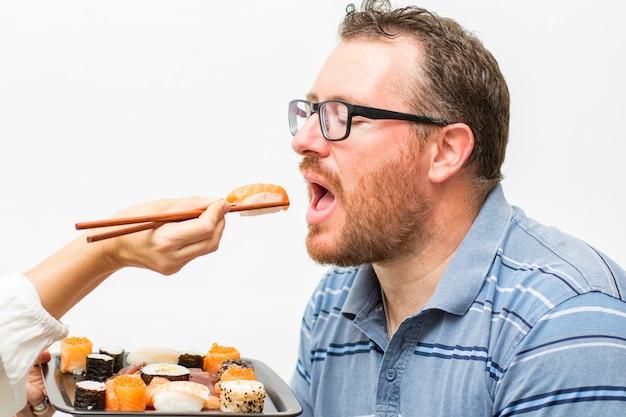 Hombre comiendo salmón nagiri con palillos