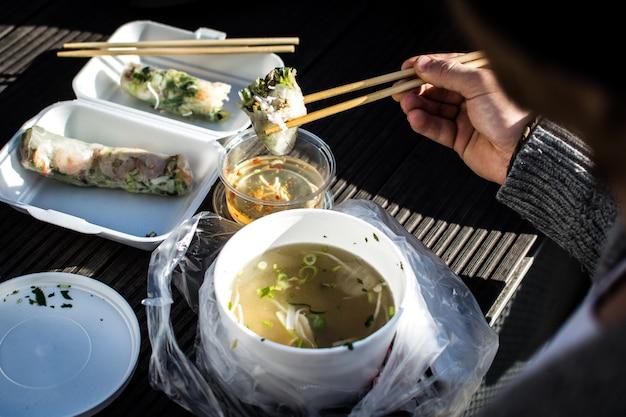 Hombre comiendo su llevar comida vietnamita con los palillos afuera