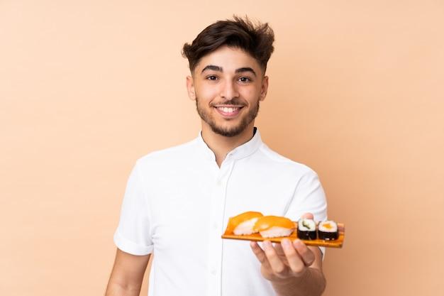 Hombre comiendo sushi aislado en la pared de color beige con expresión feliz