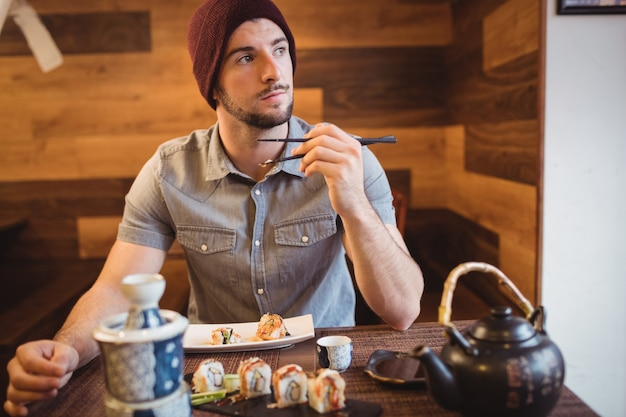 Hombre comiendo sushi en restaurante