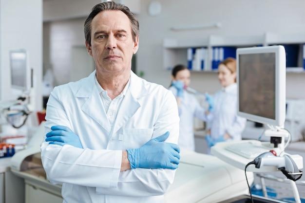 Hombre competente. practicante canoso presionando los labios y mirando directamente a la cámara mientras está de pie aislado en el fondo del laboratorio