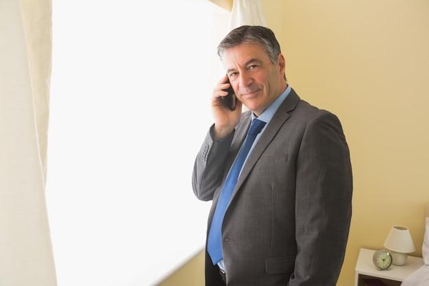 Un hombre complacido llamando a alguien con su teléfono móvil