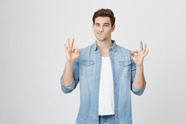 Hombre complacido seguro muestra gesto bien, aprobar o garantizar